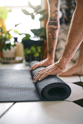 Buy stock photo Cropped shot of an unrecognisable man rolling up his yoga mat at home