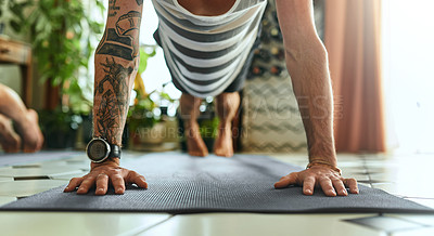 Buy stock photo Shot of an unrecognisable young man doing planks during a yoga routine at home