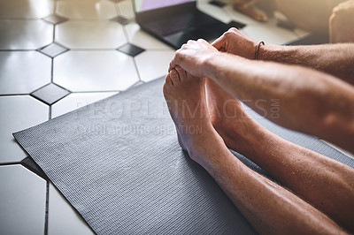 Buy stock photo Shot of an unrecognisable man using a laptop while going through a yoga routine at home