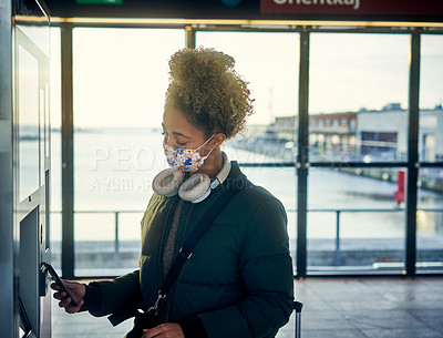 Buy stock photo Shot of a masked young woman using a smartphone at the parking meter in a subway station