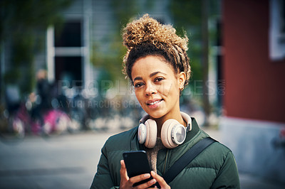 Buy stock photo Shot of a young woman using a smartphone in the city