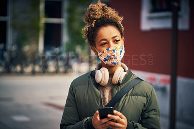 Buy stock photo Shot of a masked young woman using a smartphone in the city