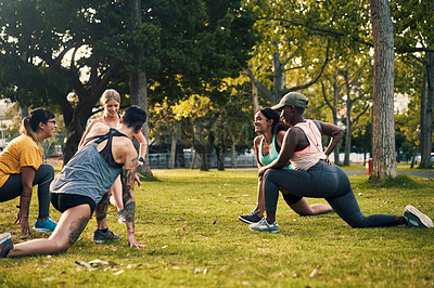 Buy stock photo Shot of a group of young women doing lunges during their workout in a park