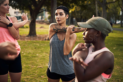 Buy stock photo Shot of a group of young women warming up before their workout in a park