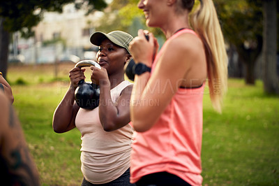 Buy stock photo Shot of a group of young women working out with kettle bells in the park