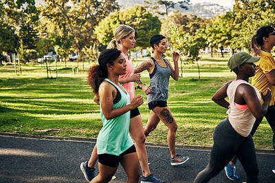Buy stock photo Shot of a group of young women going for a run in the park