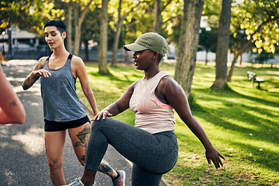 Buy stock photo Shot of a group of young women running on the spot during their workout in a park