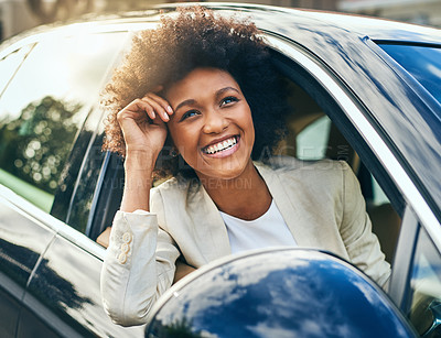 Buy stock photo Shot of a cheerful young businesswoman driving in a car to work with her arm leaning out of the vehicle during the day