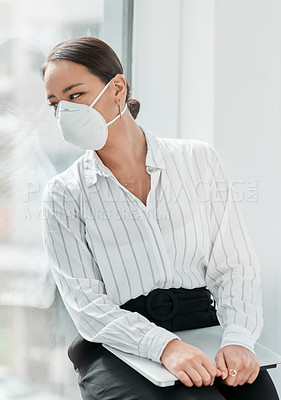 Buy stock photo Shot of a masked young businesswoman looking out of a window in a modern office
