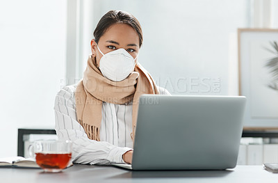 Buy stock photo Shot of a masked young businesswoman using a laptop at her desk in a modern office