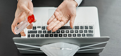 Buy stock photo Cropped shot of a businesswoman using hand sanitiser while using a laptop in a modern office