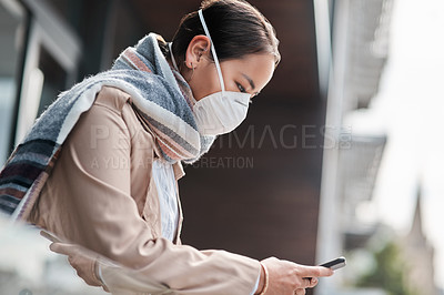 Buy stock photo Shot of a young woman wearing a mask and using a smartphone on the balcony at home
