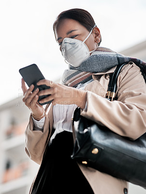 Buy stock photo Shot of a young woman wearing a mask and using a smartphone while out in the city