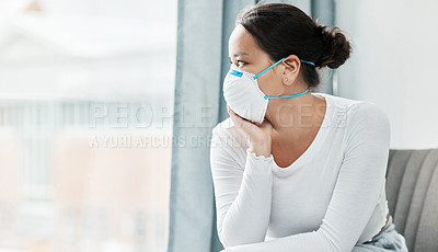 Buy stock photo Shot of a young woman wearing a mask while looking out a window at home