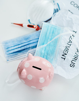 Buy stock photo Shot of a piggybank and coronavirus props against a white background