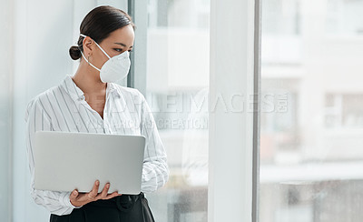 Buy stock photo Shot of a masked young businesswoman holding a laptop and looking out a window in a modern office