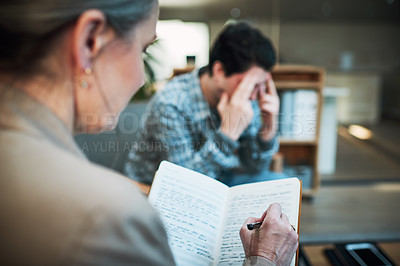 Buy stock photo Shot of a young man having a therapeutic session with a psychologist and looking upset