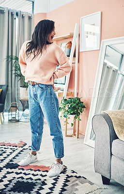 Buy stock photo Shot of a young woman looking at herself in the mirror behind her
