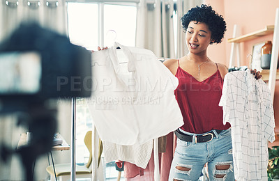 Buy stock photo Shot of a woman recording herself while holding up two clothing items