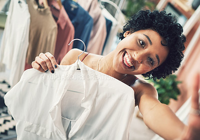 Buy stock photo Cropped shot of a woman holding up a shirt towards the camera