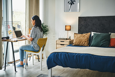 Buy stock photo Shot of a young woman cleaning her laptop while working from home