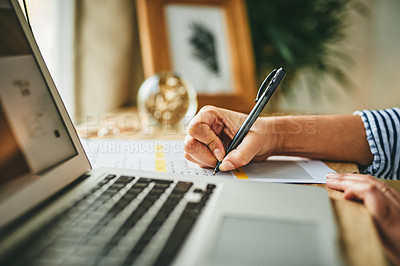 Buy stock photo Closeup shot of an unrecognisable woman writing notes while working on a laptop at home