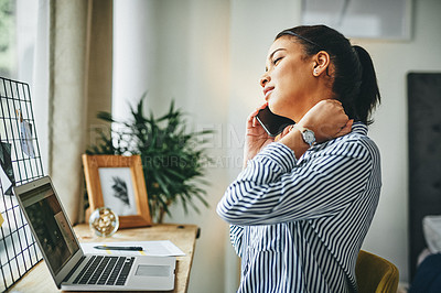 Buy stock photo Shot of a young woman rubbing her neck while talking on a cellphone at home