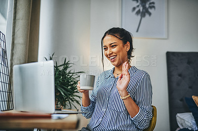 Buy stock photo Shot of a young woman making a video call on a laptop at home