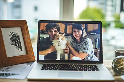 Buy stock photo Shot of a young couple and their dog having a video call with a laptop