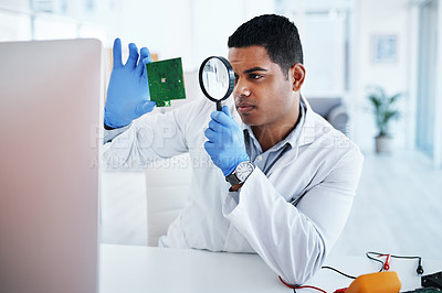 Buy stock photo Shot of a young man using a magnifying glass while repairing computer hardware in a laboratory