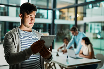 Buy stock photo Shot of a businessman using a digital tablet in an office with his colleagues sitting in the background