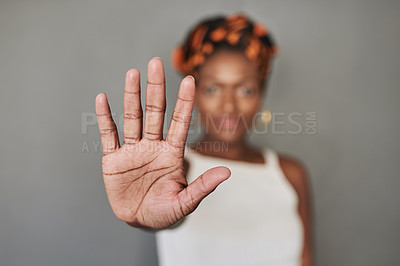 Buy stock photo Studio portrait of a young woman holding her palm out against a grey background