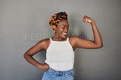Buy stock photo Studio shot of a young woman flexing her biceps against a grey background