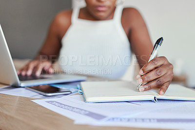 Buy stock photo Closeup shot of an unrecognisable woman writing notes while working on a laptop