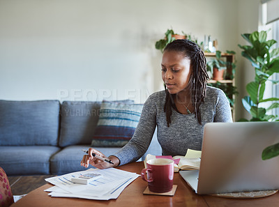 Buy stock photo Shot of a young woman using a laptop and going through documents while working from home