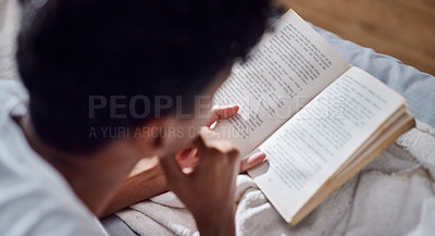 Buy stock photo Shot of a young man reading a book and relaxing on his bed at home