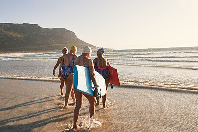 Buy stock photo Rearview shot of a group of senior women enjoying some time together at the beach