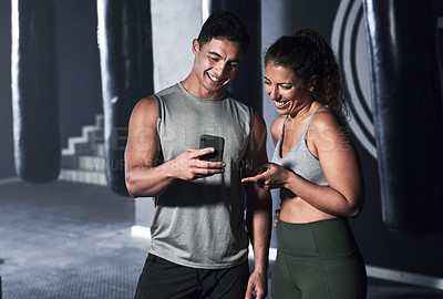 Buy stock photo Shot of two sporty people looking at something on a cellphone together in a gym