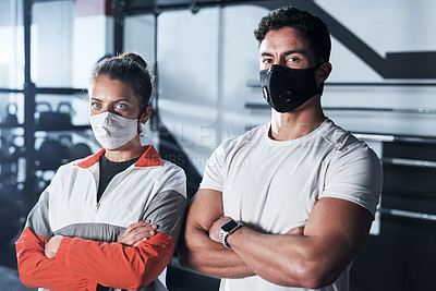 Buy stock photo Portrait of two sporty young people wearing face masks in a gym