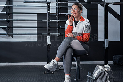 Buy stock photo Shot of a sporty young woman using a cellphone in a gym