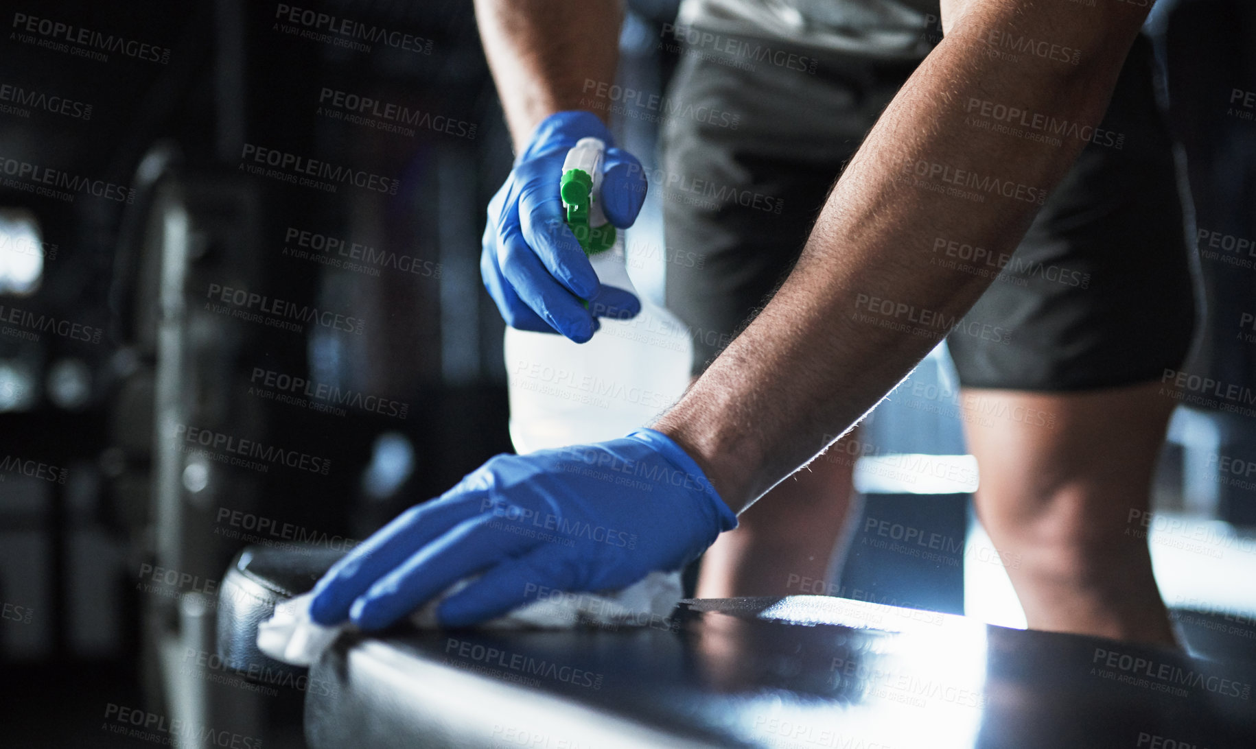 Buy stock photo Cropped shot of an unrecognisable man disinfecting the surfaces in a gym