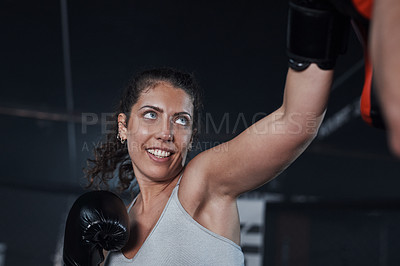 Buy stock photo Shot of a young woman practicing with her coach at a boxing gym