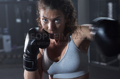 Buy stock photo Portrait of a young woman practicing her boxing routine at a gym