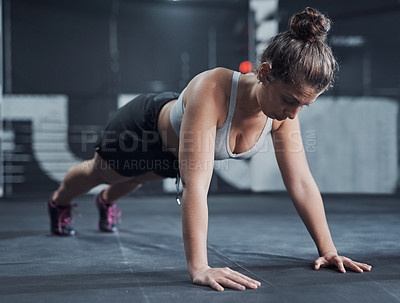Buy stock photo Shot of a young woman doing push ups at a gym