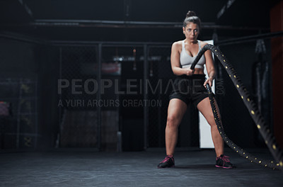 Buy stock photo Shot of a young woman working out with battle ropes at a gym