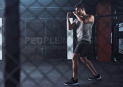 Buy stock photo Shot of a young man practicing his kickboxing routine at a gym