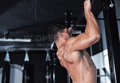 Buy stock photo Shot of a young man lifting doing pull ups at a gym