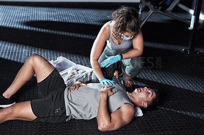 Buy stock photo Shot of a masked young woman giving an injured man first aid at the gym