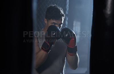 Buy stock photo Shot of a young man practicing his boxing routine at a gym