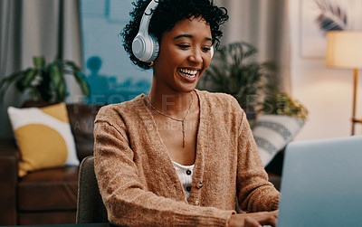 Buy stock photo Shot of a young woman wearing headphones while using a laptop at home